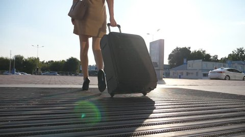 Business lady going to taxi parking from the airport with her luggage. Girl in heels stepping and roll suitcase on wheels. Woman walking with her suitcase along street. Travel concept. Slow motion
