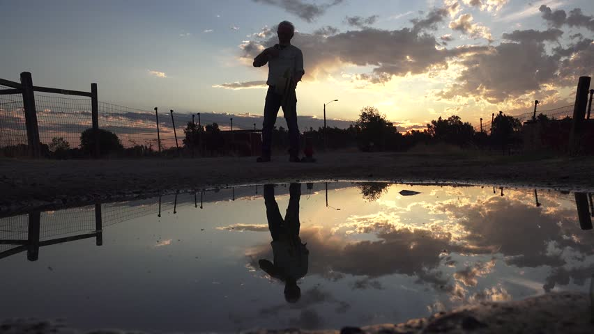 Cowboy walking at dawn or dusk carrying a lasso and a red lantern with clouds and sky reflected in a puddle of water on a dirt road. Man wearing Western hat seen in the still water.