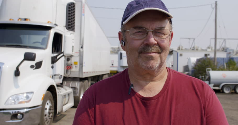2c957e4c Close up portrait of driver wearing burgundy T-shirt, cap and glasses,  looking at viewer and standing in front of truck in haulage yard.