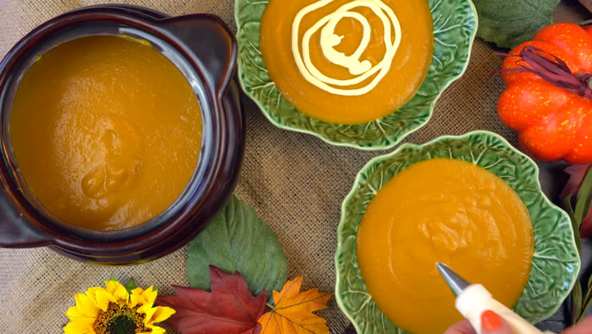 Serving hot pumpkin soup into green leaf bowls and making spider web cream decorations, on a rustic background for Happy Halloween party food.