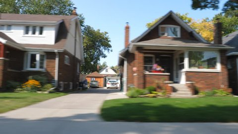 Driving past houses on suburban street in late summer. East York, Toronto, Ontario, Canada.