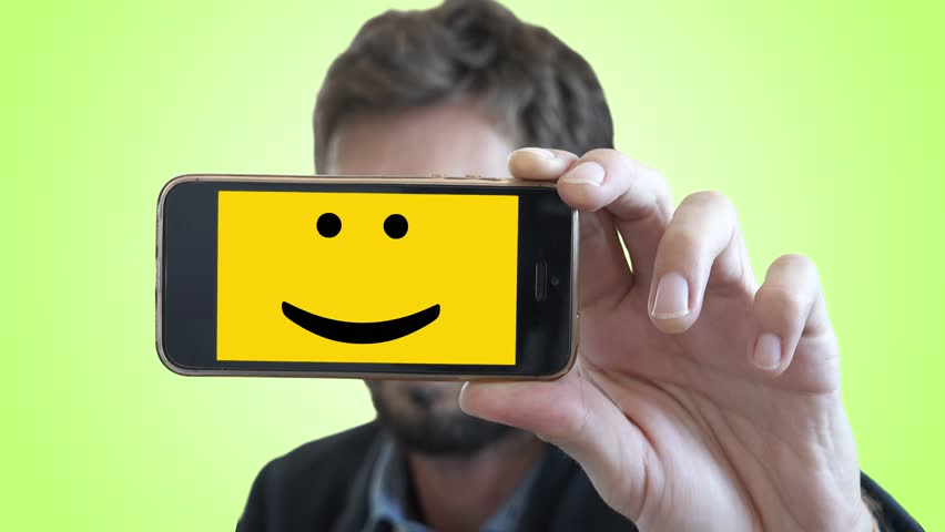 Smiley Face In Smartphone Shows Emotions of Man. Man shows his feelings through a smartphone with a Smiley face on screen