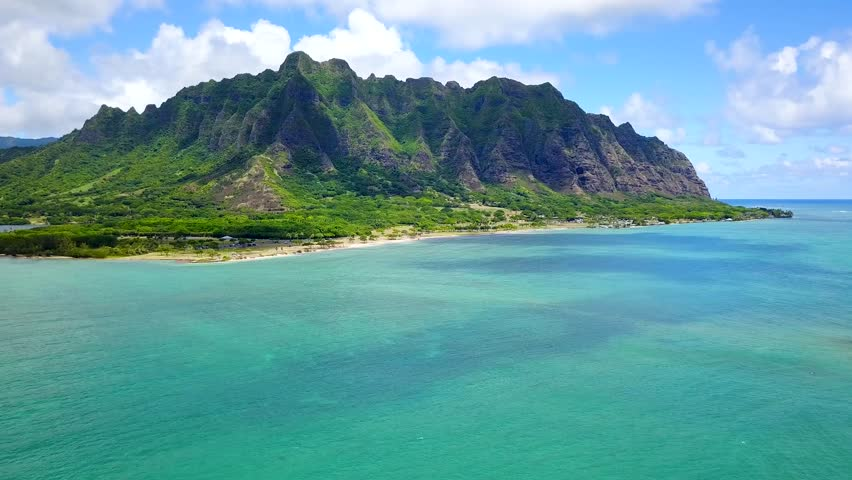Aerial Scenic flyover footage of ocean of Chinamans Hat, Oahu Hawaii.  Tropical view of Kualoa Valley, Koolau Mountain. Kaneohe Bay side. Turquoise-blue water lovely with blue sky. 4K UHD drone shot. | Shutterstock HD Video #30760324