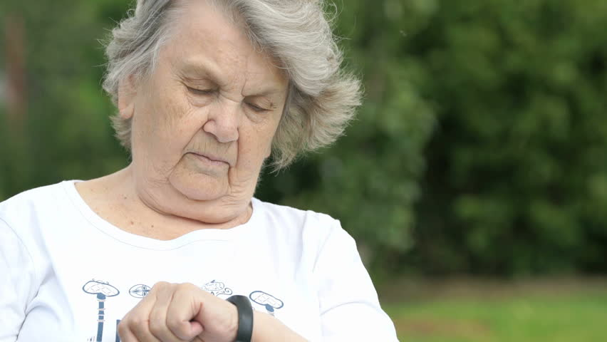 Mature elderly woman dressed in white t-shirt looks at the results of physical activity using a wristband fitness tracker then smiles and shows thumbs up sign in the background of the green park.