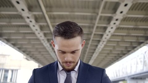 serious young man is wearing suit is raise his head, standing under bridges constructions in daytime