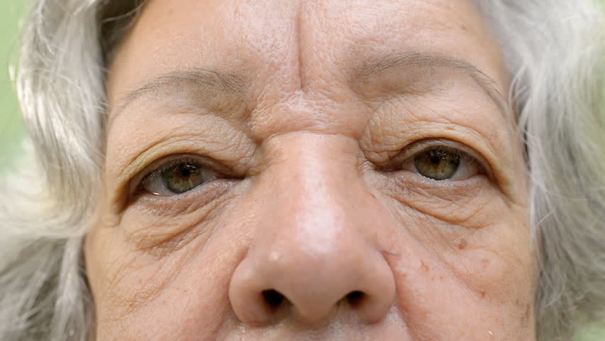 Elderly people and feelings, details of face and eyes of senior woman with white hair looking at camera. Sequence
