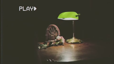 Fake VHS tape: still life with vintage objects on a table - a radio, a lamp, a yellow rose with blood stains over its petals.