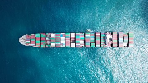 Ultra large container vessel (ULCV) at sea with a small pilot boat next to it - Aerial footage