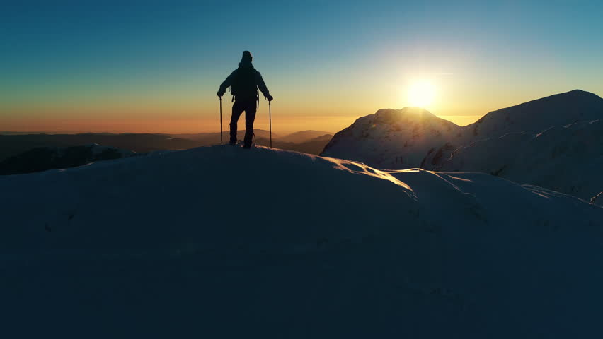 Aerial, edited - Raising above male hiker standing on top of snowy mountain and looking at beautiful sunset | Shutterstock HD Video #30810499