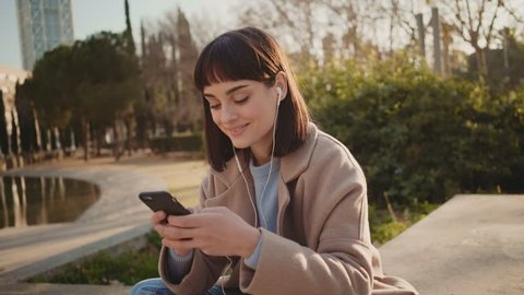 Young attractive cute millennial hipster woman chats and flirts on messenger application on smartphone while sitting outside in park in winter,concept social media, sexting and communication