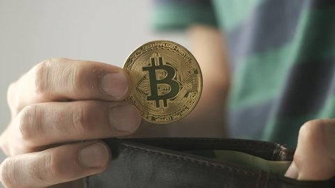 Man putting a bitcoin coin into his wallet. Bitcoin is a worldwide cryptocurrency and digital payment system.