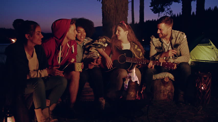 Diverse Group Of Attractive Young People Playing Guitar Around Burning Bonfire In The Woods Clapping Drinking Laughing And Joking Nature Tourism And Music Romantic Musical Getaway Concept Slow Motion #30848374