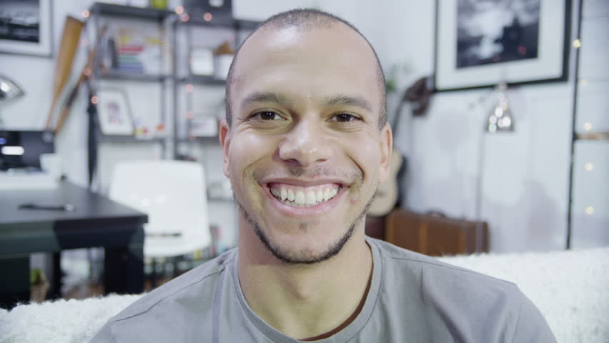 Close up shot of an attractive young man who turns his head and smiles broadly at the camera
