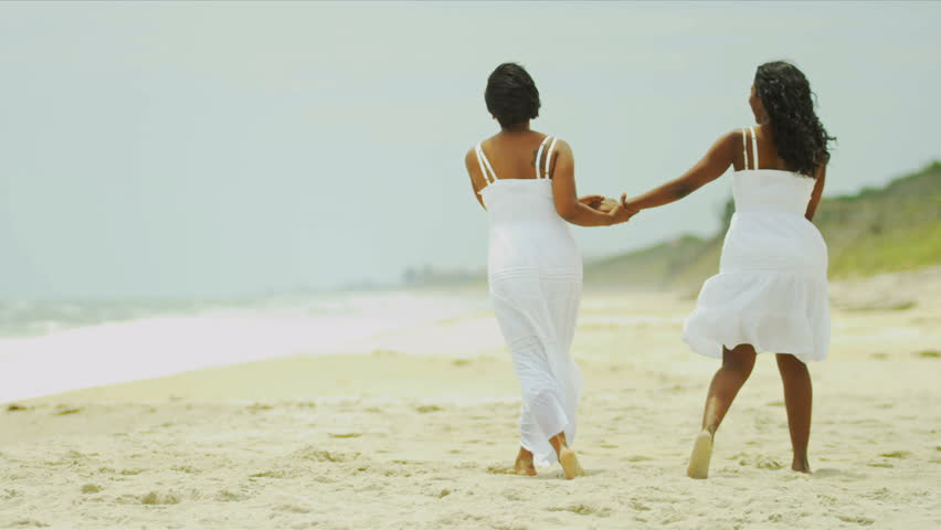 5bb6ae2a20294 Diverse mother and daughter enjoying summer holiday walking on beach