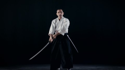 Aikido Master Wearing Traditional Samurai Hakama Clothes Takes His Japanese Sword out of Scabbard and Swings with It. He's in the Spotlight Darkness Surrounds Him. Shot Isolated on Black Background.