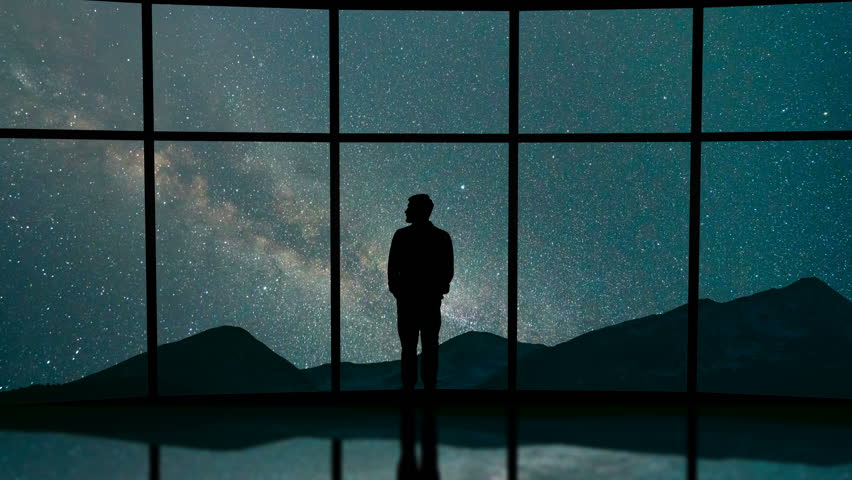 The man stand near a panoramic window on the starry sky background. time lapse