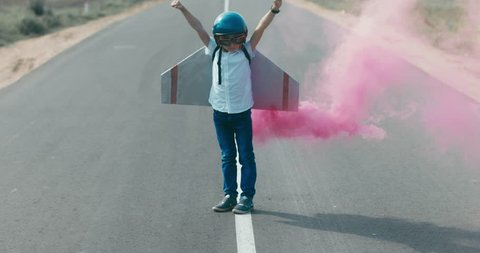 CINEMAGRAPH - seamless loop. Little boy wearing helmet and styrofoam wings standing on a skateboard on a rural road, pretending to be a pilot