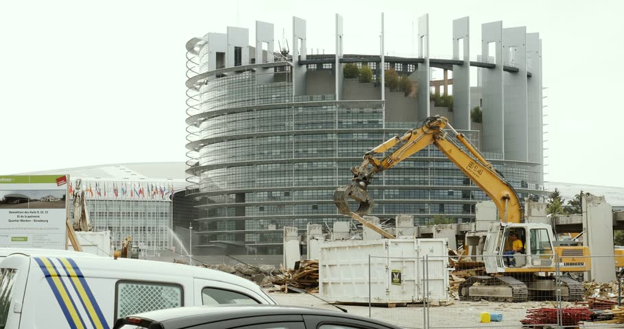 STRASBOURG, FRANCE - CIRCA 2016: Large construction site with European Parliament Headquarter building in Strasbourg in the background with Liebherr excavator working