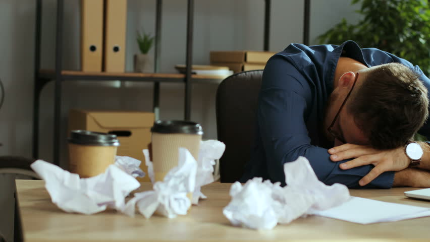 Portrait of tired business man sleeping on the office table, waking up and feeling confused in the modern office. | Shutterstock HD Video #30873184