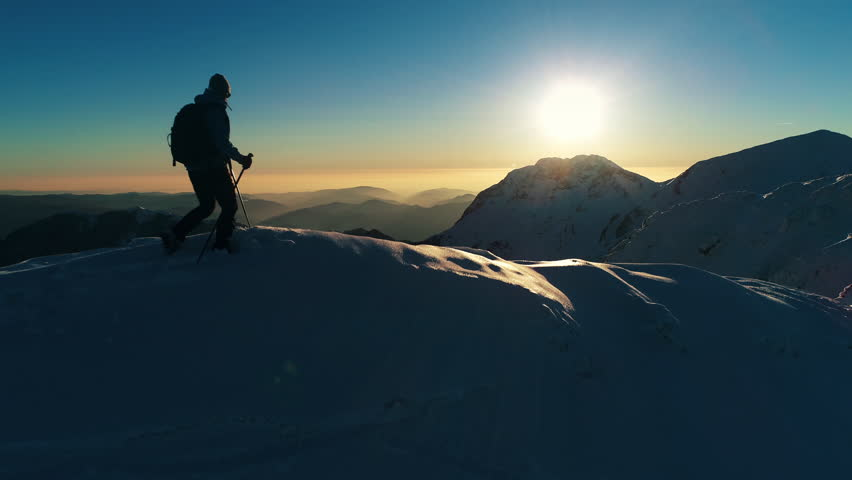 Aerial - Close up shot of young winter hiker arriving on top of snowy mountain peak at sunset, edited version | Shutterstock HD Video #30874264