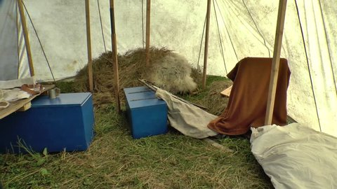 Interior of tent field hospital with bunk and medical tools