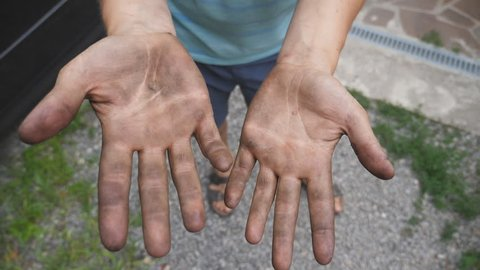 Mechanic shows hands in fuel oil after the done work. Then starts rubbing his dirty hands. Close up Slow motion