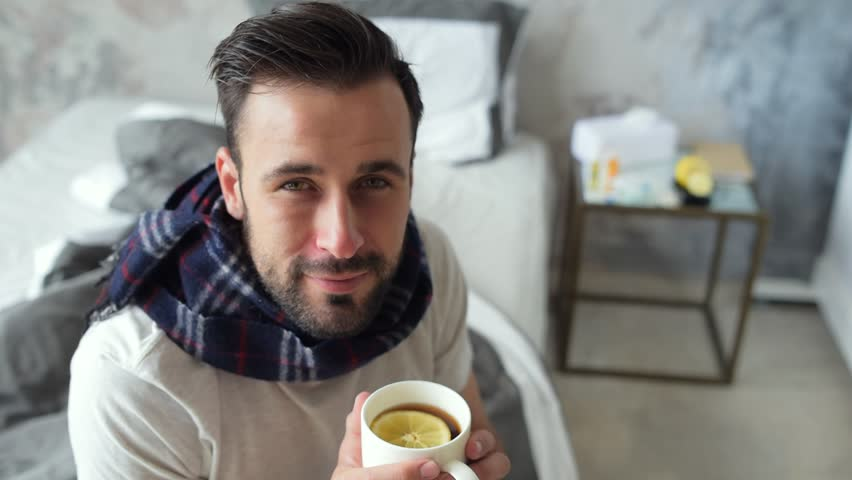 Smiling sick guy looking into camera while drinking tea | Shutterstock HD Video #30907264