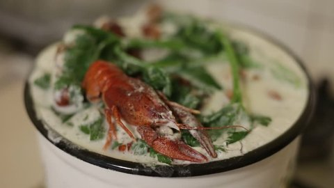 Preparation of boiled crawfish in a pan with milk and celery. cooked red crayfish in a saucepan. Close-up shot.