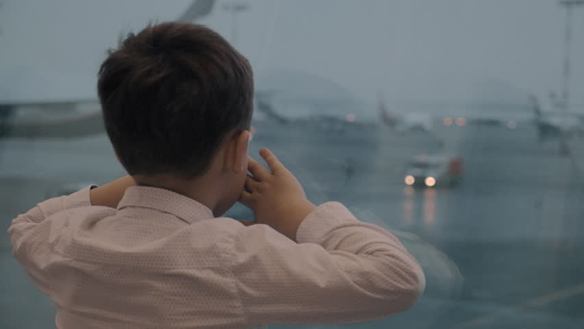Slow motion shot of a child clinging to the window in airport terminal. He staring at planes on parking and waiting for his flight #30917524