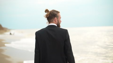 handsome bearded man walking along seaside in business suit backside in slow motion
