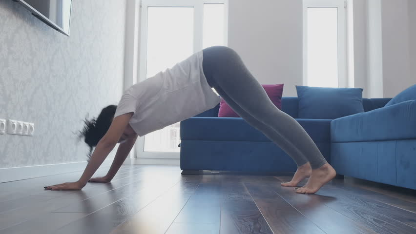 Attractive lady makes yoga exercise in the hall