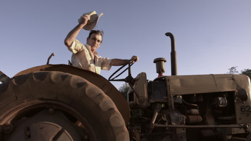 59.94fps (It can be in slow motion) happy farmer with a hat driving tractor