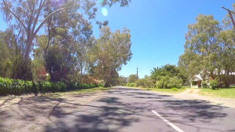 Vehicle POV, driving along the McLaren Vale Tourist Drive, South Australia, with sun reflections and lens flare.