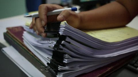 Officer Businessman searching data in Stacks of papers files on work desk in office, business report paper or piles of unfinished documents notation with clips on offices desk, Business concept