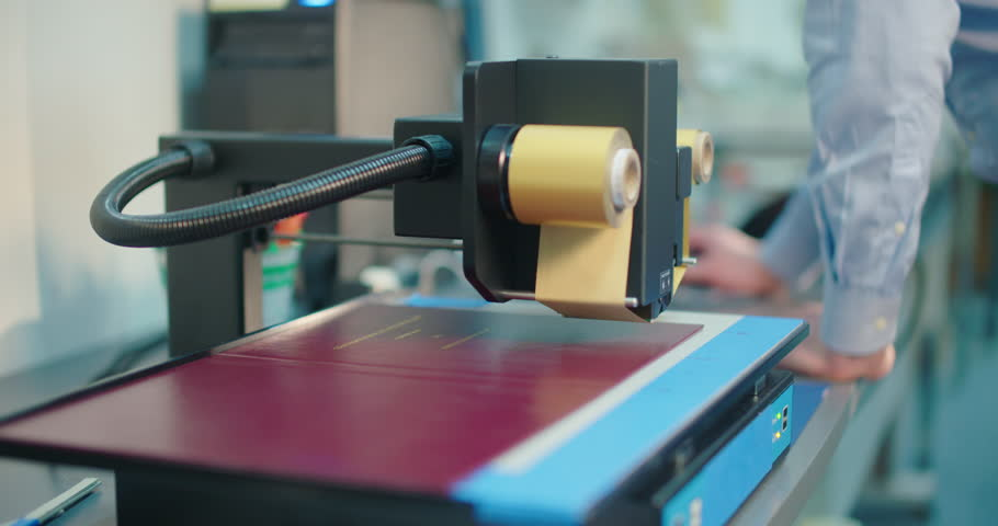 Employee Running Book Embossing Machine on Hardcover. a view moves from left to right as an employee runs a hardcover embossing machine  | Shutterstock HD Video #30971344