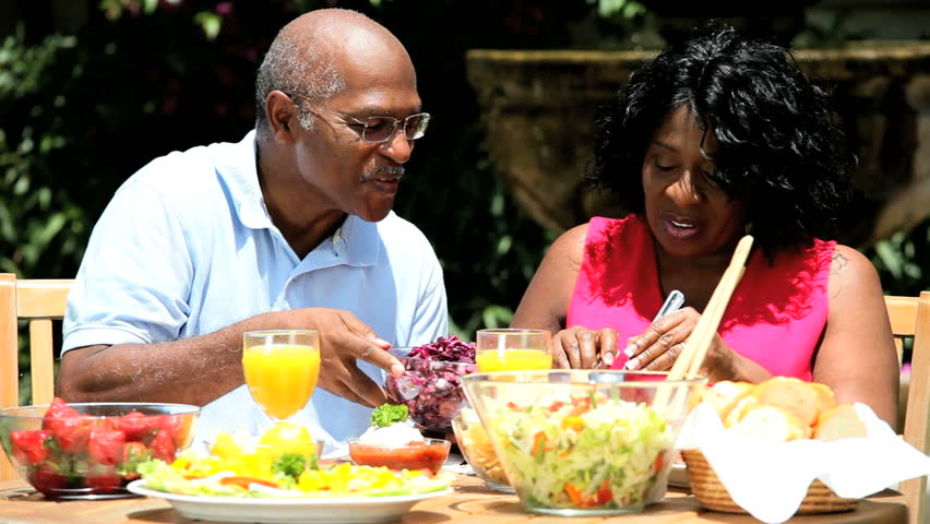 Retired ethnic couple sharing a healthy lunch