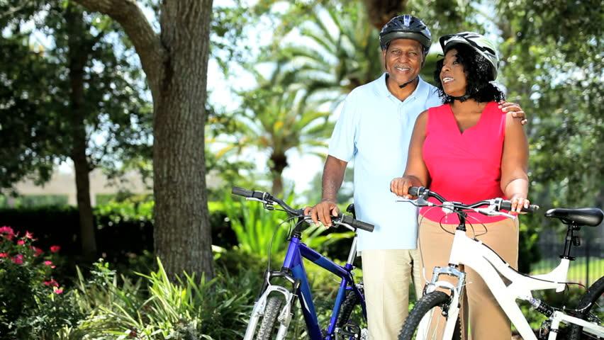 Senior ethnic successful couple start cycling