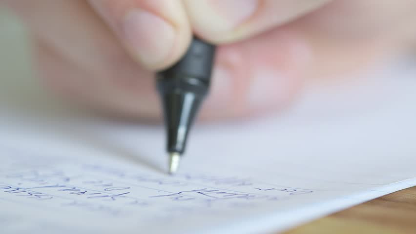 Extreme close up of a pen writing exam essay or letter, shallow depth of field.