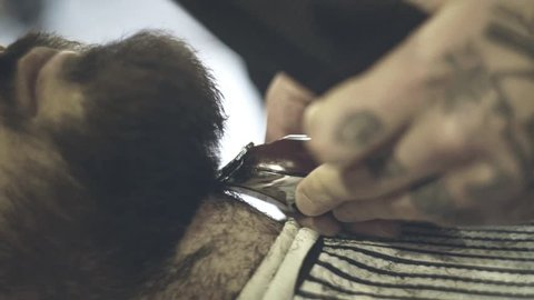 Barber shave with razor. Male barber trimming beard of client with clipper at barbershop. Close up of shaving beard man