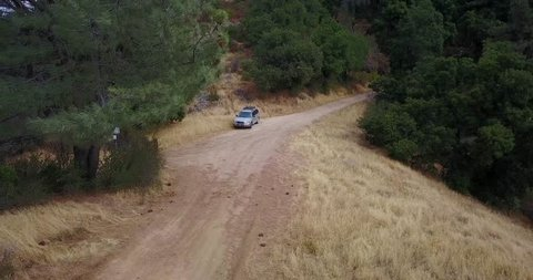 Aerial drone following subaru forester on dirt road. Figueroa Mountain. Santa Barbara, California.