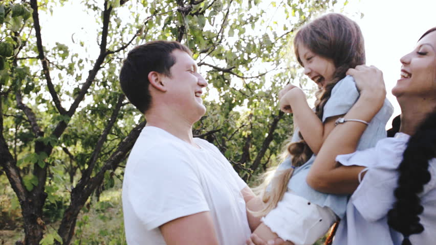 Parents tickle their laughing daughter