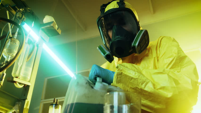 In the Underground Drug Laboratory Clandestine Chemist Wearing Protective Mask and Coverall Mixes Chemicals. He Pours Liquid From Canister into Bowl to Make New Batch of Synthetic Narcotics.