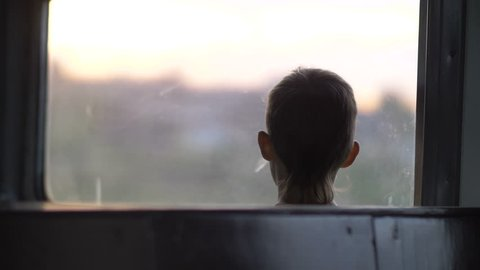 boy rides on a train in the evening, sunny glare, back view