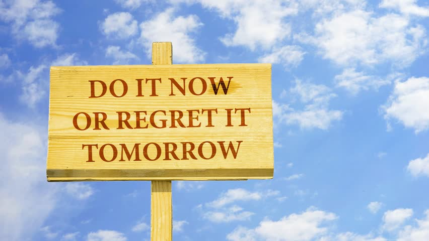 Do it now or regret it tomorrow. Words on a wooden sign against time lapse clouds in the blue sky.
