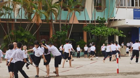 DA NANG, VIETNAM - OCTOBER 8, 2016: Schoolboys of Vietnam. Children are having fun outside the fence in the school yard.