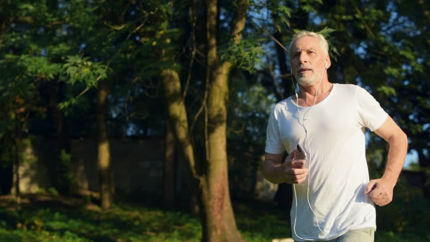 Confident senior man jogging in the park #31034944