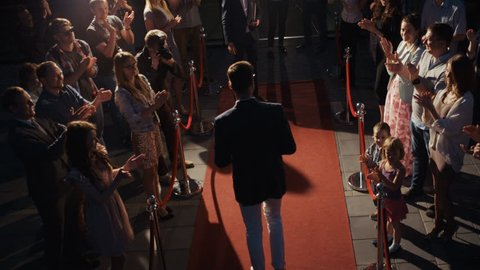 Side-view scene, award ceremony concept, young man in business clothes walking across red carpet with photographers media press people applause fame fans grant prize triumph trophy handshaking reward