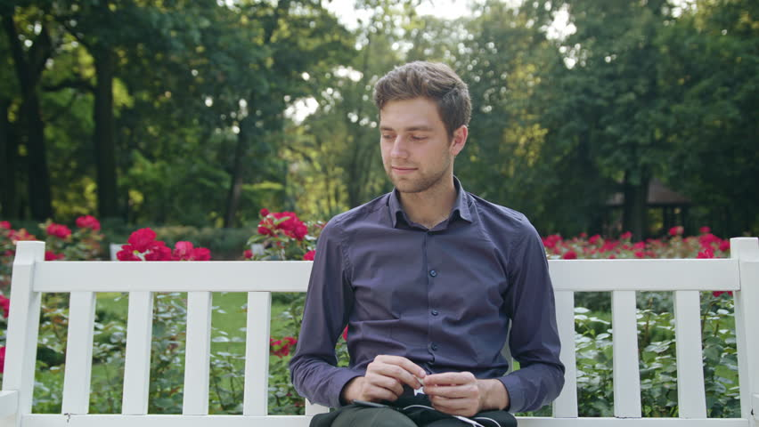 A young man sitting on a white bench in the park using a phone listening to music. Medium shot   Shutterstock HD Video #31059880
