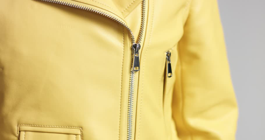 Hot sexy young female model unzipping her soft yellow leather biker jacket to show white ribbed top
