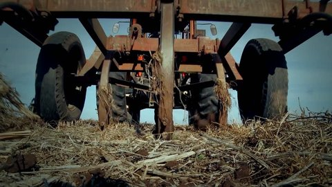 Farmer Plowing the Field. Low View. Zoom In.